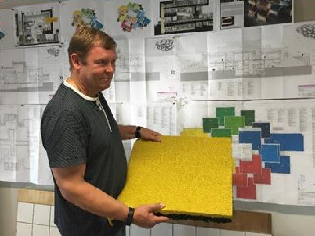 Projektleder Kim Peter Nissen fra K.G. Hansen med et stykke af faldunderlaget, som er lavet af gummisko-rester. Underlaget består af et bærelag, som er ca. 2,5 cm tykt og et farvet toplag på ca. 1,5 cm. Foto: LEGO House